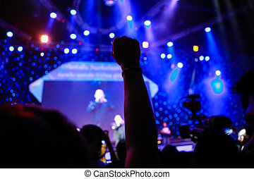 Cheering and hands raised at a live music concert