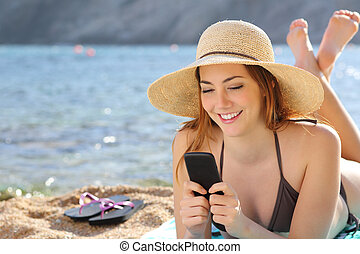 Woman on the beach texting a smart phone in summer with the...