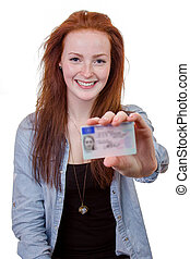 Young woman showing her driver's license - 16 to 18 year old...