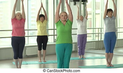 Warming up - Women performing mountain pose and wide-legged...