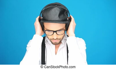 fashionable man wearing hat and headphones listening to the...