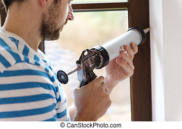 Man with caulking gun - Man applying silicone sealant with...