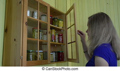 lady cabinet canned food - Lady take glass jar with canned...
