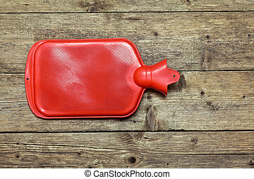 Hot water bottle or bag on wooden background