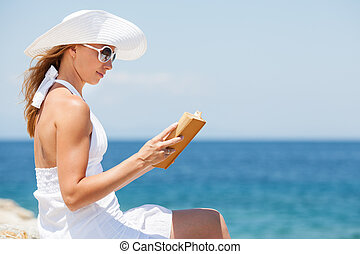 Young woman reading book on the beach