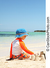 One caucasian boy playing with sand at tropical beach