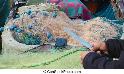 Fisherman Repairs Fishnets