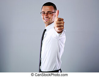 Side view portrait of a happy businessman showing thumb up over gray background