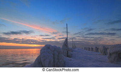 Unusual frozen pier and ocean at beautiful sunrise light...