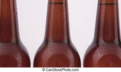Conveyor Bottles of beer with drops isolated on white...