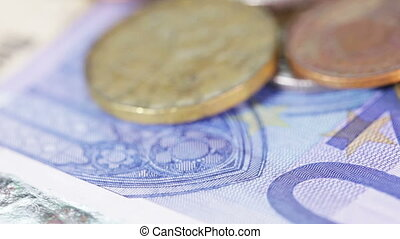 Banknotes and coins on rotating surface on burlap background