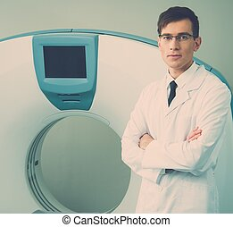 Young doctor standing near computed tomography scanner in a...