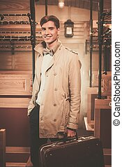 Handsome young man with suitcase in coat inside vintage...