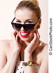 Beautiful blond pinup woman with sunglasses happy smiling & looking at camera on white background portrait