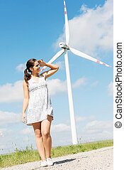 Happy teen girl next to wind turbineEco energy concept