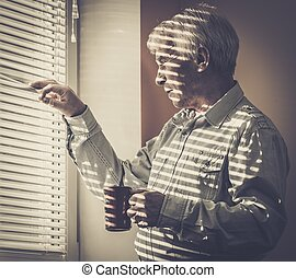 Senior man with cup looking out the window through jalousie