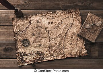 Compass, book and inkwell on a vintage map