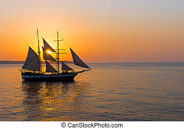 Romantic sunset with sailing ship - A romantic sunset with a...