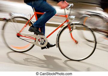 Man on orange bike in city in blurred motion