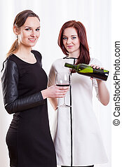 Elegant ladies with wine on the party