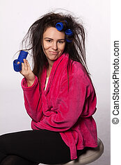 Young woman with curlers - Young woman in bathrobe with...