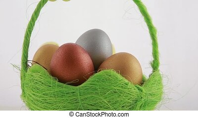 Golden Easter eggs in green basket. White background