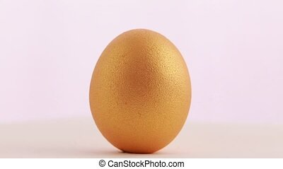 Golden Easter egg isolated over white background Rotation...