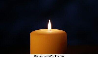Candle on navy blue background