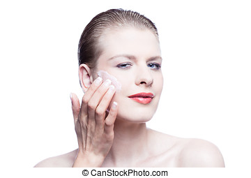 Woman applying face cream isolated on white