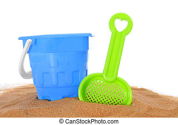 beach toys on the sand - toy shovel and beach pail on the...