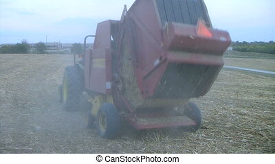 Round Baler at Dusk - Round baler finishes processing and...