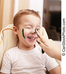 Little boy laughing as mother paints his face - Little boy...