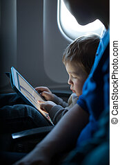 Little boy playing with a tablet in an airplane - Little boy...