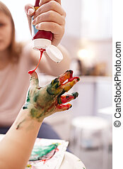 Young child playing with finger paints holding out its hand...