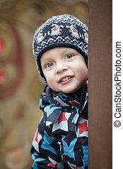 Cute little boy peering around a door - Cute little boy in a...