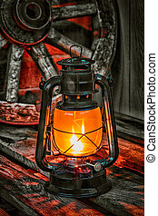 kerosene lamp against the background wagon wheel - kerosene...