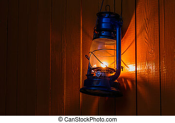 old kerosene lantern hanging on the yellow wooden wall - The...