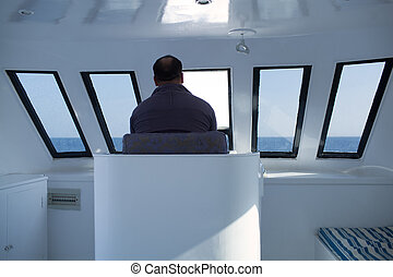 Man navigating a boat sitting in the captains chair during a...