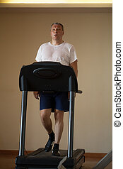 Middle-aged man working out on a treadmill - Fit attractive...