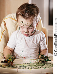 Creative little boy playing with finger paint creating a...