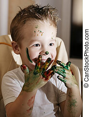 Excited little boy playing with finger paints - Excited...
