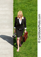 businesswoman walking barefoot - high angle view of mid...