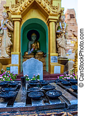Shwedagon Pagoda - Praying place with candle holders at...