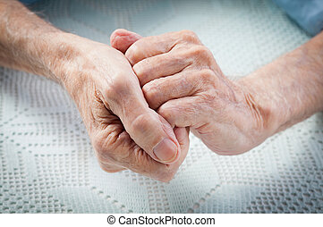 Care is at home of elderly. Old people holding hands.