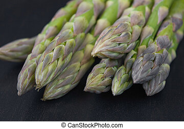 Asparagus - Bunch of green asparagi on dark back ground