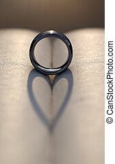Wedding Ring Casting a Heart Shadow Between Pages of a Book...