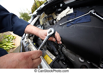 Hands of auto mechanic with wrench. Car repair service.