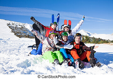 Sitting friends with snowboards lifting hands up - Five...