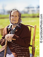 Old woman relaxing - Very old woman with head scarf sitting...