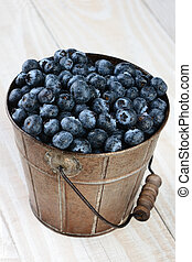 Bucket of Blueberries on Rustic Table - Closeup of a bucket...